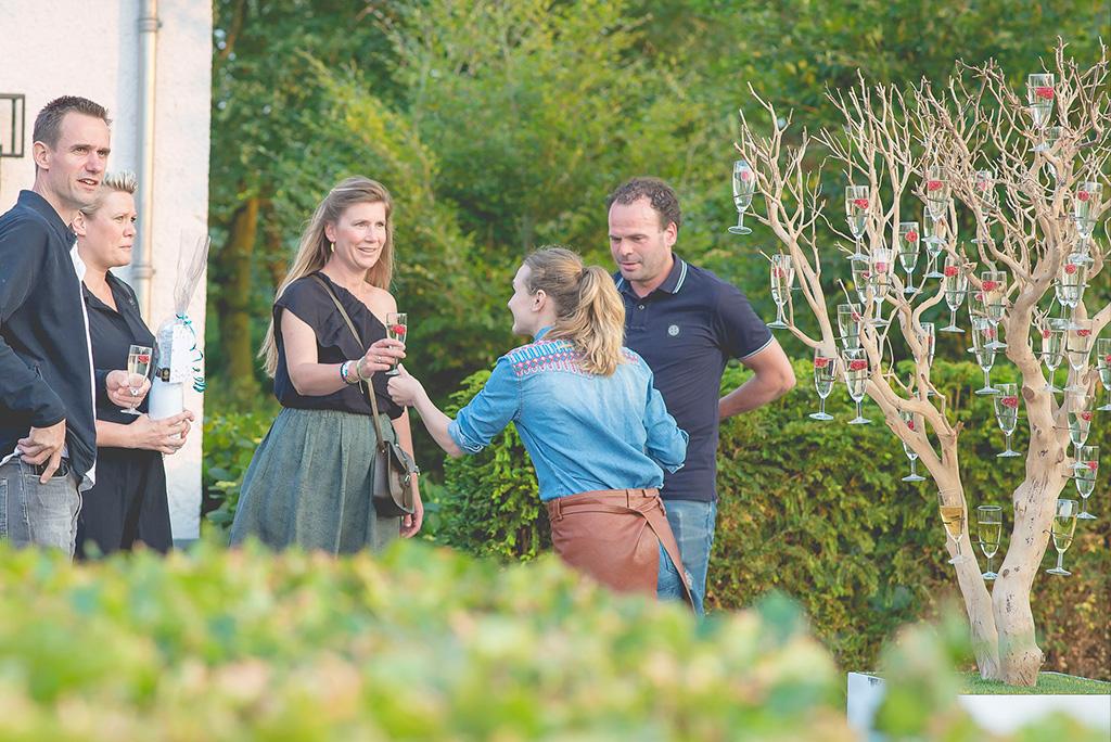 Ober met champagneboom op prive tuinfeest