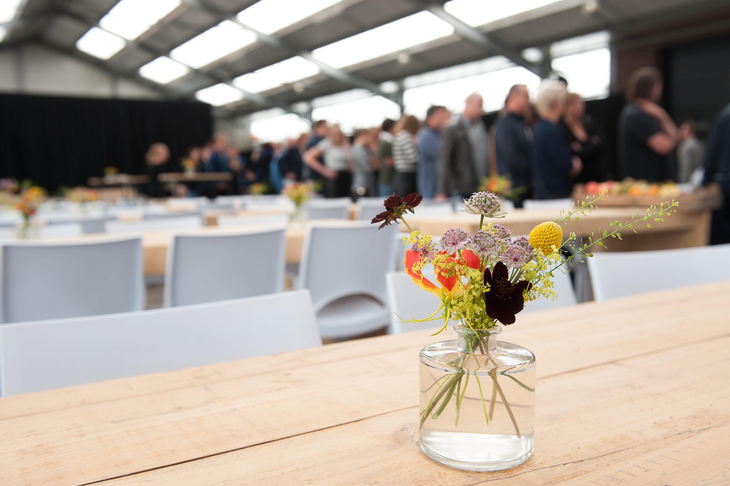 Een bloemstukje staat op tafel bij een uitvaart op locatie